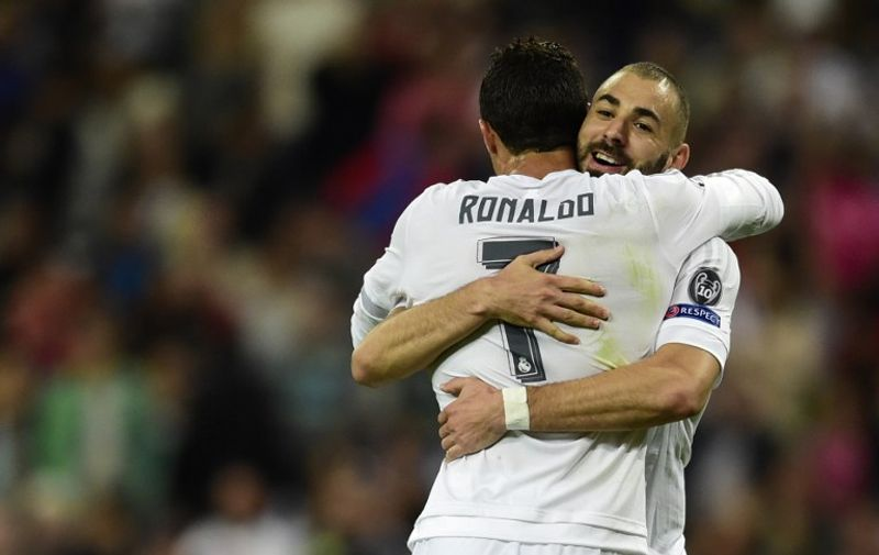 Real Madrid's French forward Karim Benzema (R) celebrates a goal with Real Madrid's Portuguese forward Cristiano Ronaldo during the UEFA Champions League group A football match Real Madrid CF vs FC Shakhtar Donetsk at the Santiago Bernabeu stadium in Madrid on September 15, 2015. AFP PHOTO/ JAVIER SORIANO