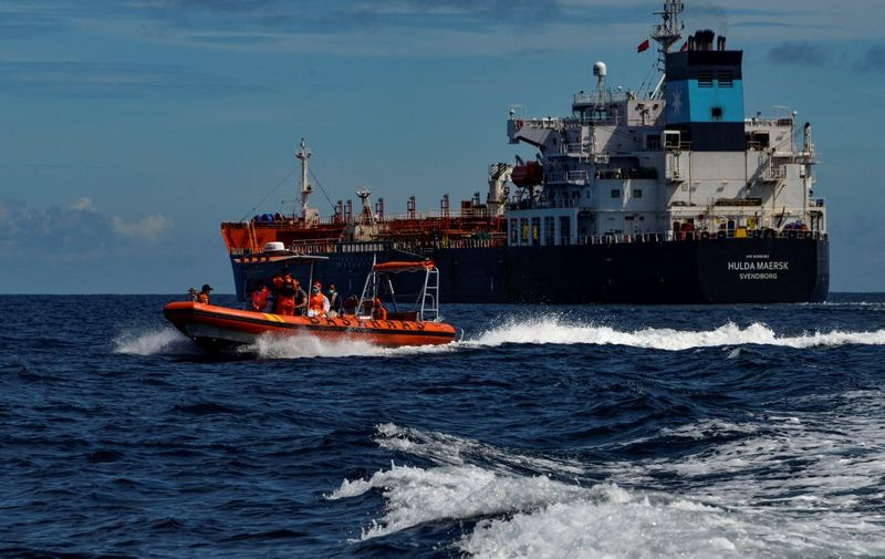 A dinghy (L) from Indonesia's National Search And Rescue Agency (BASARNAS) returns to their vessel after evacuating a Russian crew member from the Danish tanker Hulda Maersk (R) for medical reasons, at sea off the coast of Aceh on April 27, 2021. (Photo by CHAIDEER MAHYUDDIN / AFP)