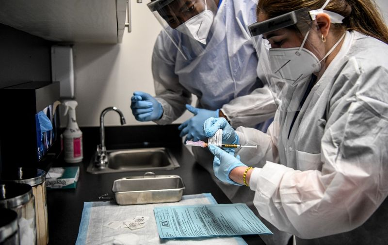 Yaquelin De La Cruz (R) and  Hari Leon Joseph (L) prepare a COVID-19 vaccine for vaccination at the Research Centers of America in Hollywood, Florida, on August 13, 2020. (Photo by CHANDAN KHANNA / AFP)