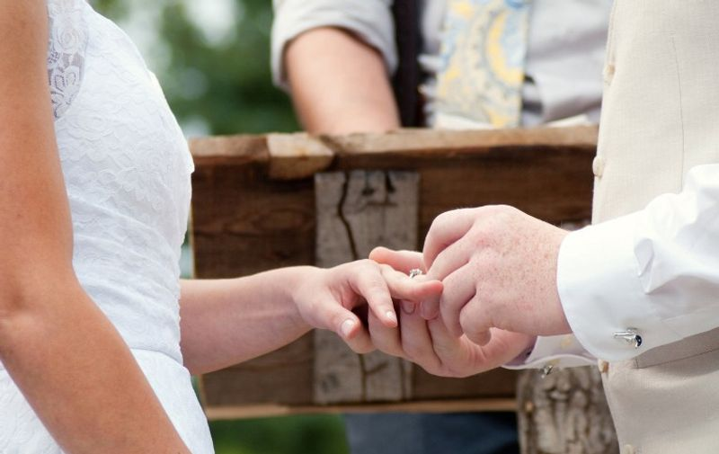 Close up of couple putting on rings at wedding ceremony