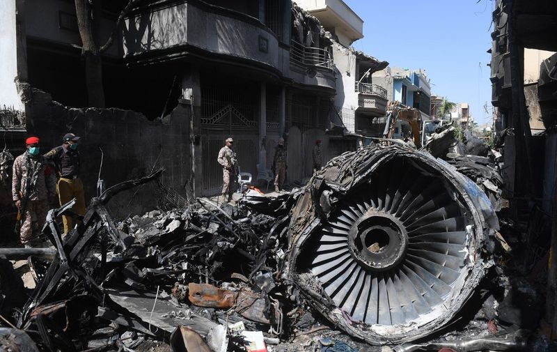 (FILES) In this file photo taken on May 24, 2020, security personnel stand beside the wreckage of a plane at the site after a Pakistan International Airlines aircraft crashed in a residential area days before, in Karachi. - A plane crash which killed 97 people in Pakistan last month was because of human error by the pilot and air traffic control, according to an initial report into the disaster released on June 24. (Photo by Asif HASSAN / AFP)