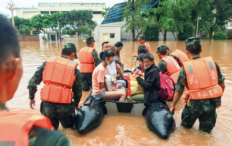 This photo taken on August 18, 2020 shows rescuers evacuating residents at a flooded area following heavy rains in Leshan in China's southwestern Sichuan province. - Floods in mountainous southwest China have washed away roads and forced tens of thousands from their homes, with authorities warning on August 19 the giant Three Gorges Dam was facing the largest flood peak in its history. (Photo by STR / AFP) / China OUT