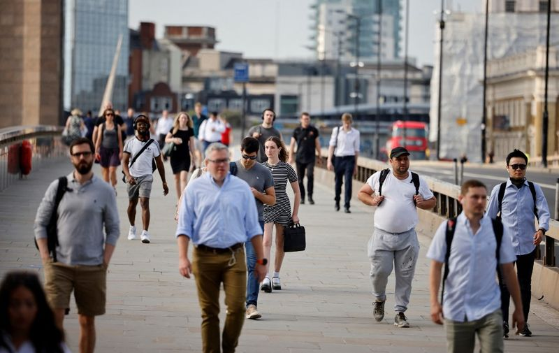 """Commuters not wearing facemasks cross London Bridge in London on July 19, 2021. - Virtually all pandemic restrictions were lifted in England today but """"freedom day"""" was met with deep concern from scientists as coronavirus cases surge across the nation -- and around the world. (Photo by Tolga Akmen / AFP)"""