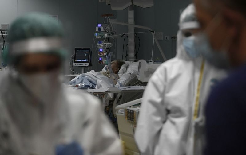 Medical staff wearing protective gear (Front) work next to a patient laying in bed (Rear) at the Intensive Care Unit (ICU) for COVID-19 patients at the Casalpalocco Clinical Institute in Rome on November 18, 2020. - The coronavirus has killed at least 1,339,130 people since the outbreak emerged in China last December, according to a tally from official sources compiled by AFP at 1100 GMT on November 18, 2020. (Photo by Filippo MONTEFORTE / AFP)