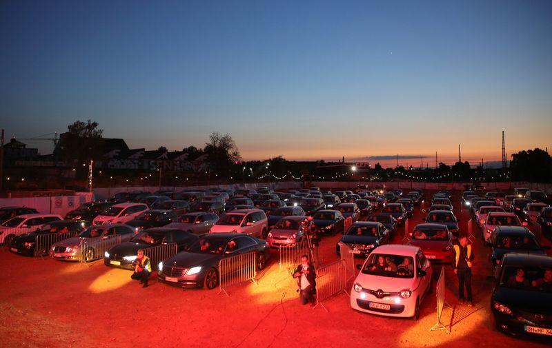 """BONN, GERMANY - MAY 15: Cars parked in line and follow German singer Heino's performance during the first BonnLive drive-in concert at Am Westwerk during the Coronavirus crisis on May 15, 2020 in Bonn, Germany. The project """"BonnLive Autokonzerte"""" is a series of drive-in concerts with musicians of different genres. The area provides space for about 200 cars. Drive-ins are becoming an increasingly popular venue for singers, theater groups, and even churches to hold events while adhering to Coronavirus lockdown measures. Two peoples are allowed to attend per vehicle and the attendees must remain in their cars. (Photo by Andreas Rentz/Getty Images)"""
