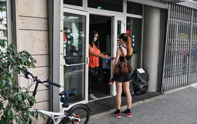 "Arianna Sisto (L), owner of the ""Crossfit Trastevere"" gym in the Trastevere district of Rome, hands plastic shoe covers to a customer on May 25, 2020 in Rome, as the country eases its lockdown aimed at curbing the spread of the COVID-19 infection, caused by the novel coronavirus. - Swimming pools, gyms and fitness clubs reopened in Italy on May 25, 2020, marking a new stage in the deconfinement that begun three weeks ago. (Photo by ANDREAS SOLARO / AFP)"