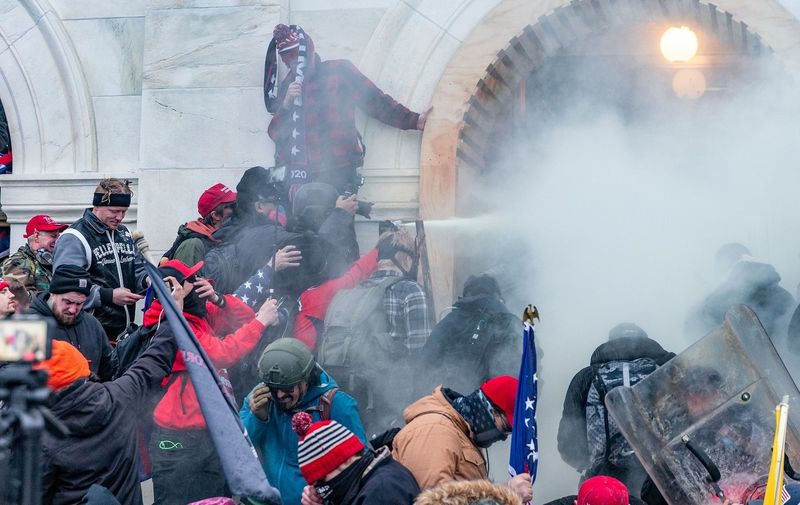 Rioters use tear gas while clash with police trying to enter Capitol building through the front doors. Rioters broke windows and breached the Capitol building in an attempt to overthrow the results of the 2020 election. Police used buttons and tear gas grenades to eventually disperse the crowd. Rioters used metal bars and tear gas as well against the police. Pro-Trump Riot in Washington DC, District of Columbia, United States - 06 Jan 2021,Image: 581665913, License: Rights-managed, Restrictions: , Model Release: no
