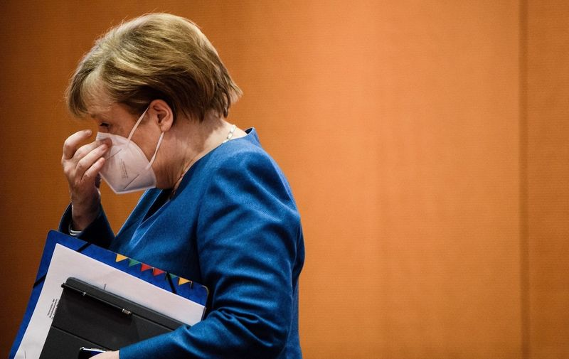 German Chancellor Angela Merkel touches her face mask as she arrives for the beginning of the weekly meeting of the German Federal cabinet in the conference hall of the Chancellery in Berlin, Germany, 06 January 2021. A day after stricter coronavirus measures have been decided, the Chancellor and the governments minister are expected to discuss the slow vaccine distribution. Cabinet meeting at the Chancellery, Berlin, Germany - 06 Jan 2021,Image: 581313278, License: Rights-managed, Restrictions: , Model Release: no
