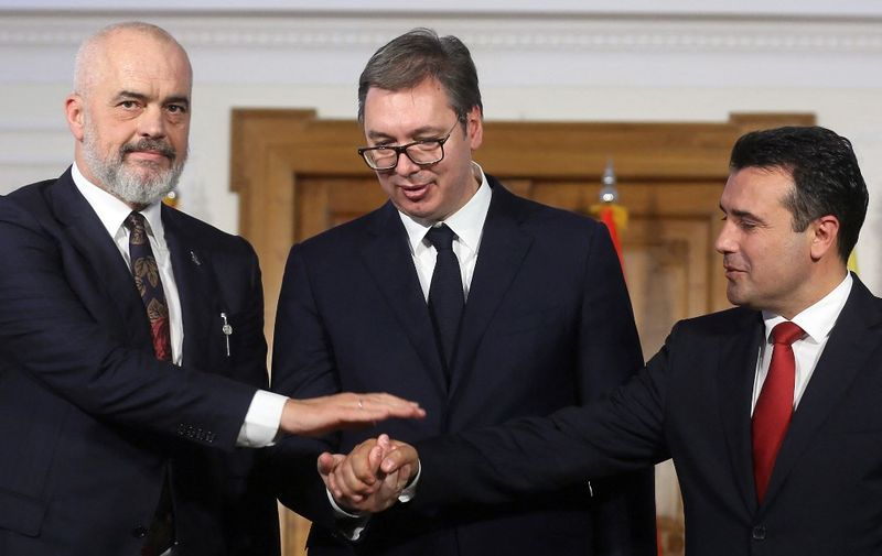 Albanian Prime Minister Edi Rama (L), Serbian President Aleksandar Vucic (C) and North Macedonian Prime Minister Zoran Zaev shake hands after their joint press conference after their meeting to discuss easing of customs barriers between their countries in Novi Sad, Serbia, on October 10, 2019. (Photo by OLIVER BUNIC / AFP)