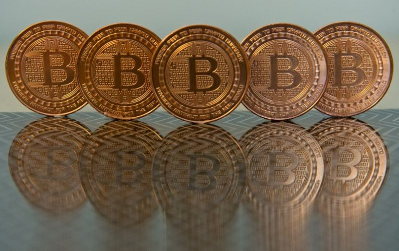 This June 17, 2014 photo taken in Washington, DC shows bitcoin medals. Bitcoin uses peer-to-peer technology to operate with no central authority or banks; managing transactions and the issuing of bitcoins is carried out collectively by the network. AFP PHOTO / Karen BLEIER / AFP / KAREN BLEIER