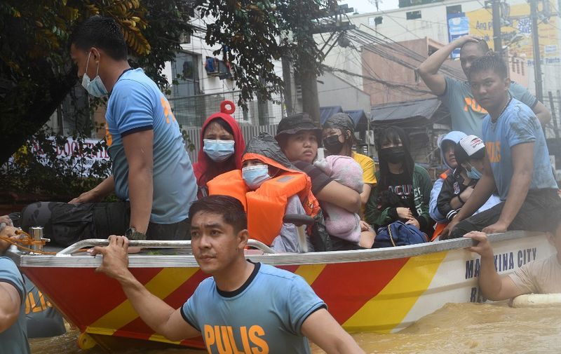 Rescuers evacuate residents from their flooded homes after Typhoon Vamco hit, in Marikina City, suburban Manila on November 12, 2020. (Photo by Ted ALJIBE / AFP)