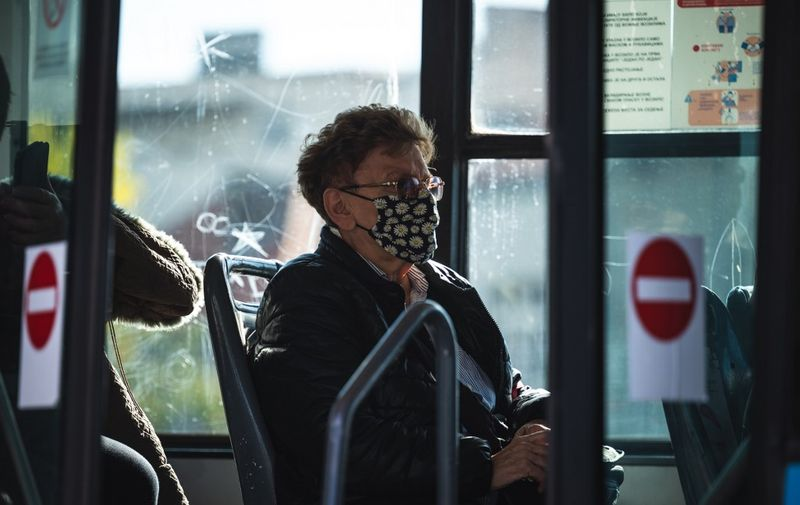 A woman wearing protective face mask sits in a bus in Belgrade on October 21, 2020. - As coronavirus cases rise both globally and in the region, Serbian government is tightening mask-wearing rules and restricting opening hours of bars and restaurants. (Photo by Andrej ISAKOVIC / AFP)