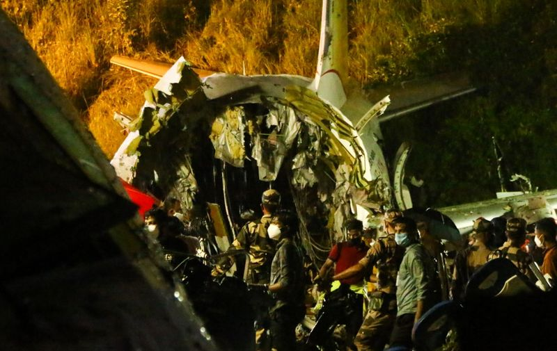 First responders inspect the wreckage of an Air India Express jet, which was carrying more than 190 passengers and crew from Dubai, after it crashed by overshooting the runway at Calicut International Airport in Karipur, Kerala, on August 7, 2020. - At least 14 people died and 15 others were critically injured when a passenger jet skidded off the runway after landing in heavy rain in India, police said on August 7. (Photo by Favas JALLA / AFP)