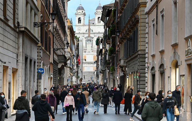 A general view shows people walk across the Via dei Condotti luxury shopping street, with the Trinita dei Monti church in background, in downtown Rome on November 14, 2020, during the Covid-19 pandemic caused by the novel coronavirus. - The Italian government imposed tighter restrictions on another five regions on November 10 as it tries to stem escalating new cases of coronavirus, while still resisting a nationwide lockdown. (Photo by Alberto PIZZOLI / AFP)