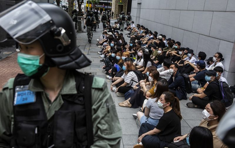 Riot police detain a group of people (R) during a protest in the Causeway Bay district of Hong Kong on May 27, 2020, as the city's legislature debates over a law that bans insulting China's national anthem. - Hong Kong police placed a dragnet around the financial hub's legislature on May 27 and fired pepper-ball rounds in the commercial district as they tried to stamp out protests against a bill banning insults to China's national anthem. (Photo by ISAAC LAWRENCE / AFP)