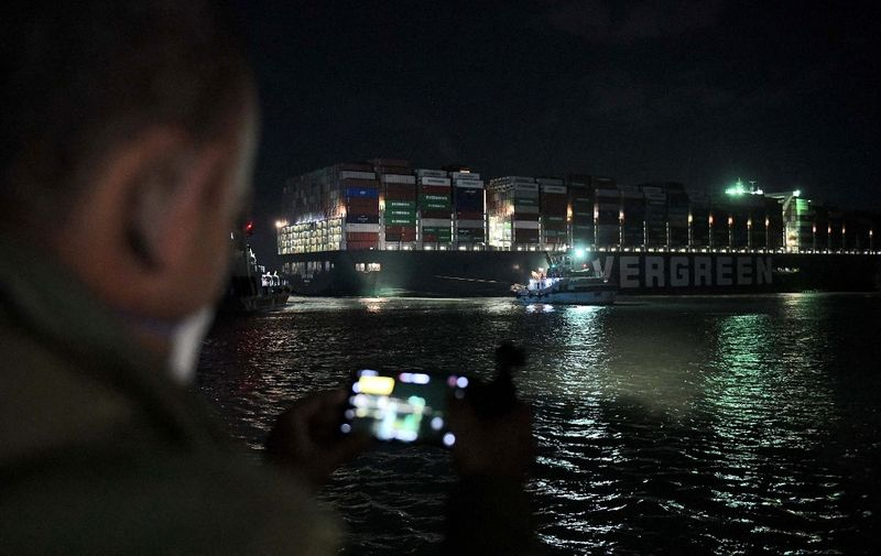 This picture taken late on March 27, 2021 shows a view of a man using his phone to take a picture of tugboats by the Panama-flagged MV 'Ever Given' (operated by Taiwan-based Evergreen Marine) container ship, which has been wedged diagonally across the span of the canal about six kilometres north of the Suez Canal's entrance by the Red Sea port city of Suez since March 23, blocking the waterway in both directions. (Photo by Ahmed HASAN / AFP)