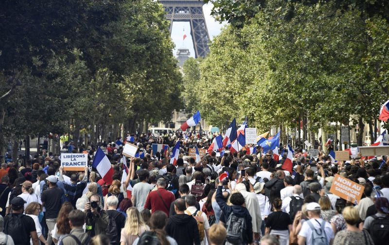 People take part in a national day of protest against French legislation making a Covid-19 health pass compulsory to visit a cafe, board a plane or travel on an inter-city train, in Paris on July 31, 2021. - The legislation passed by parliament the week before has sparked mass protests in France but the government is determined to press ahead and make the health pass a key part of the fight against Covid-19. (Photo by Bertrand GUAY / AFP)
