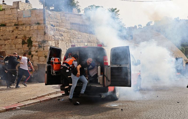 Palestinian medics evacuate wounded protesters as Israeli security forces fire tear gas in Jerusalem's Old City on May 10, 2021, as a planned march marking Israel's 1967 takeover of the holy city threatened to further inflame tensions. (Photo by EMMANUEL DUNAND / AFP)