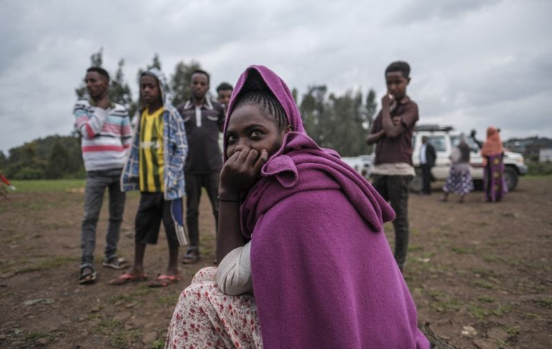 An internally displaced woman sits at the entrance of a camp in the town of Azezo, Ethiopia, on July 12, 2021. The camp hosts Ethiopians as well as Eritrean refugees uprooted by the ongoing war in the region of Tigray. - The July 13 clashes at Mai Aini represented just the latest example of how the Tigray war has upended life for many thousands of Eritrean refugees, who for more than two decades had come to see the region as a sanctuary from their oppressive homeland. (Photo by EDUARDO SOTERAS / AFP)