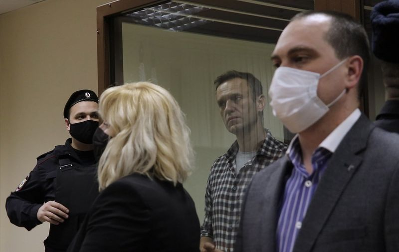 MOSCOW, RUSSIA - FEBRUARY 20, 2021: Alexei Navalny's lawyers Olga Mikhailova and Vadim Kobzev (L-R front) and opposition activist Alexei Navalny (C background) attend the announcement of the verdict in the defamation case at an offsite hearing of Russia's Magistrates' court at Moscow's Babushkinsky District Court. The court has found Navalny guilty of defaming WWII veteran Ignat Artyomenko and has ordered to pay a 850,000 ruble ($ 11,477) fine. Video screen grab. Press Office of Moscow's Babushkinsky District Court/TASS  A STILL IMAGE TAKEN FROM VIDEO PROVIDED BY A THIRD PARTY. EDITORIAL USE ONLY,Image: 592293729, License: Rights-managed, Restrictions: , Model Release: no