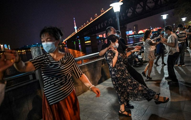 """People wearing facemasks dance in a park next to Yangtze River in Wuhan, China's central Hubei province on May 27, 2020. - China's foreign minister on May 24 said the country was """"open"""" to international cooperation to identify the source of the disease, but any investigation must be led by the World Health Organization and """"free of political interference"""". (Photo by Hector RETAMAL / AFP)"""