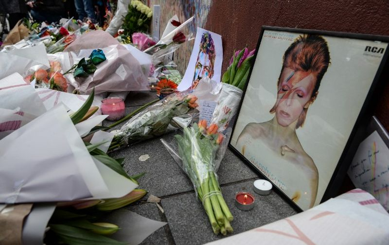 """Tributes are seen beneath a mural of British singer David Bowie, following the announcement of Bowie's death, in Brixton, south London, on January 11, 2016. British music icon David Bowie died of cancer at the age of 69, drawing an outpouring of tributes for the innovative star famed for groundbreaking hits like """"Ziggy Stardust"""" and his theatrical shape-shifting style.   AFP PHOTO / CHRIS RATCLIFFE / AFP / CHRIS RATCLIFFE"""