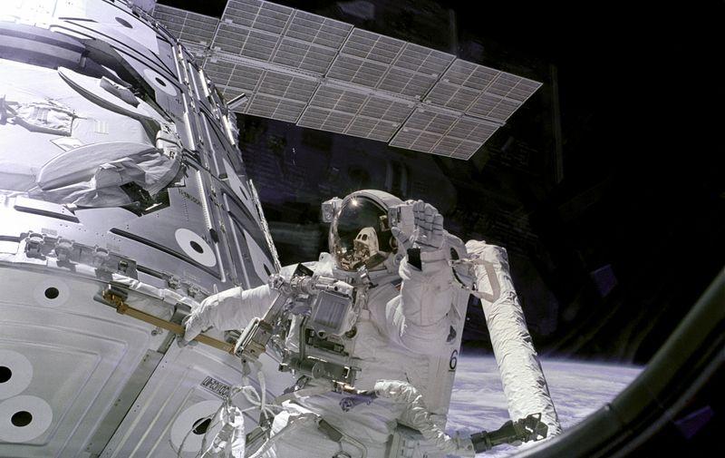 """Američki astronaut James Newman, koji je član posade na misiji STS-88 tijekom svoje """"svemirske šetnje"""". Newman se drži za rukohvat ISS-a, a pritom maše kameri koja se nalazi unutar ISS-a."""