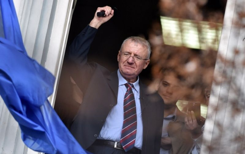 Serb  ultranationalist leader Vojislav Seselj waves at supporters on November 12, 2014 after arriving at his Radical Serb Party (SRS) headquarters in Zemun, near Belgrade . Ailing Serb leader Seselj, who has been released from the UN Yugoslav war crimes tribunal, arrived on November 12 from the Netherlands to Serbia. The International Criminal Tribunal for the former Yugoslavia (ICTY) last week ordered Seselj's release so he could return home for cancer treatment as he awaits a verdict on alleged war crimes during the Balkan wars. Seselj, accused of leading ethnic Serb volunteers in persecuting Croats, Muslims and other non-Serbs during the 1990s wars, underwent colon cancer surgery in December.  AFP PHOTO / ANDREJ ISAKOVIC