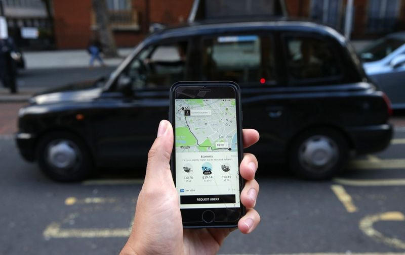 (FILES) In this file photo taken on September 22, 2017 A woman poses holding a smartphone showing the App for ride-sharing cab service Uber in London. - London's transport authority on November 25, 2019 refused to renew an operating licence for the ride-hailing giant Uber because of safety and security concerns. (Photo by Daniel LEAL-OLIVAS / AFP)
