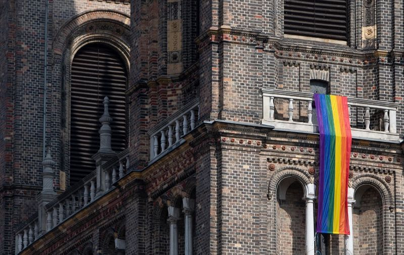 A LGBT rainbow flag hangs from on the steeple of the parish church in the Breitenfeld quarter in Vienna, on March 25, 2021. - The Catholic church of the parish of Hard is one of many in Austria which decided to fly the rainbow flag in solidarity with the LGBT community after the Vatican ruled last month that the Church couldn't bless same-sex partnerships. (Photo by ALEX HALADA / AFP) / TO GO WITH AFP STORY OF JASTINDER KHERA