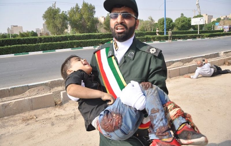 This picture taken on September 22, 2018 in the southwestern Iranian city of Ahvaz shows a member of Iran's Revolutionary Guards Corps (IRGC) carrying an injured child at the scene of an attack on a military parade that was marking the anniversary of the outbreak of its devastating 1980-1988 war with Saddam Hussein's Iraq. Dozens of people were killed with dozens others wounded in an attack in the southwestern Khuzestan province on September 22 targeting on an army parade commemorating the anniversary of the 1980-1988 Iran Iraq war, state media reported. / AFP PHOTO / ISNA / Behrad GHASEMI / ìThe erroneous mention[s] appearing in the metadata of this photo by Shayan HAJI NAJAF has been modified in AFP systems in the following manner: [Behrad Ghasemi] instead of [Shayan Haji Najfi ]. Please immediately remove the erroneous mention[s] from all your online services and delete it (them) from your servers. If you have been authorized by AFP to distribute it (them) to third parties, please ensure that the same actions are carried out by them. Failure to promptly comply with these instructions will entail liability on your part for any continued or post notification usage. Therefore we thank you very much for all your attention and prompt action. We are sorry for the inconvenience this notification may cause and remain at your disposal for any further information you may require.î