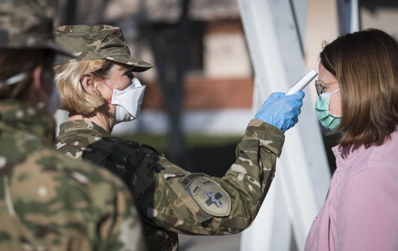 Members of Medical Unit of Slovenian Army measure body temperature prior entering the facilities for treatment of coronavirus patients set at the Edvard Peperko Army Barracks in Ljubljana on March 17, 2020, as many countries around the world go into lockdown in an attempt to stem the spread of  the novel virus COVID-19. (Photo by Jure Makovec / AFP)