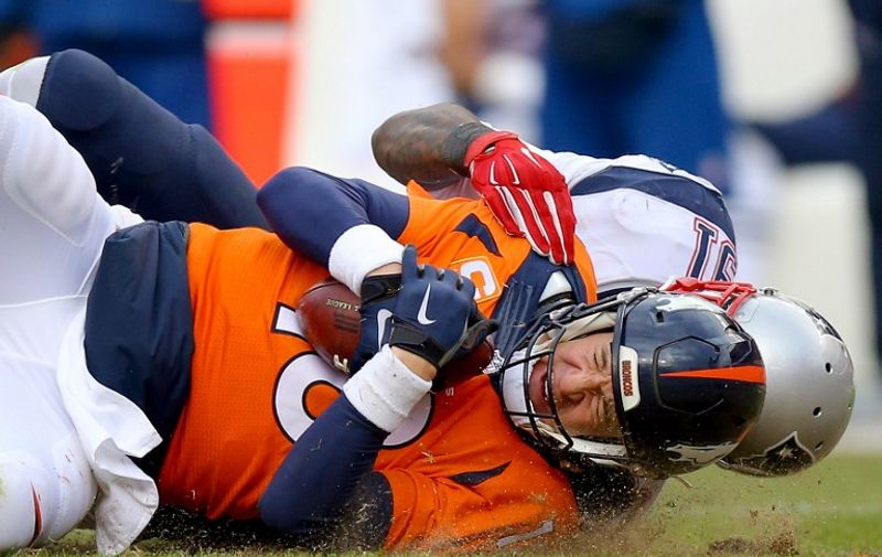 DENVER, CO - JANUARY 24: Peyton Manning #18 of the Denver Broncos is sacked by Jamie Collins #91 of the New England Patriots in the second half in the AFC Championship game at Sports Authority Field at Mile High on January 24, 2016 in Denver, Colorado.   Justin Edmonds/Getty Images/AFP
