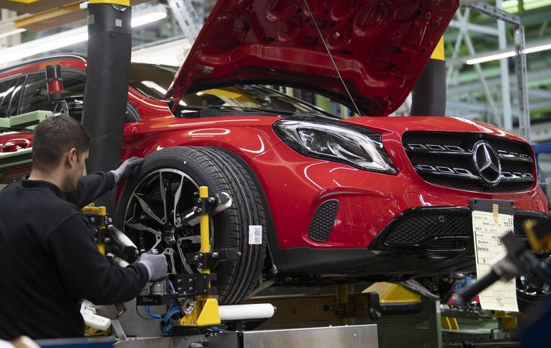 An employee mounts a wheel on a Mercedes Benz A Class on the assembly line at the Daimler AG factory in Rastatt, southwestern Germany, on February 4, 2019. - Daimler posts 2018 financial results on an annual press conference in Frankfurt Germany, on February 6, 2019. (Photo by THOMAS KIENZLE / AFP)