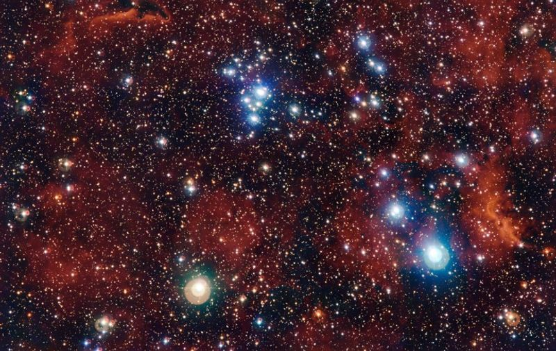 """A handout photo released on June 29, 2015 by the European Southern Observatory shows a rich view of an array of colourful stars and gas which was captured by the Wide Field Imager (WFI) camera, on the MPG/ESO 2.2-metre telescope at ESO's La Silla Observatory in Chile. It shows a young open cluster of stars known as NGC 2367, an infant stellar grouping that lies at the centre of an immense and ancient structure on the margins of the Milky Way.  AFP PHOTO / ESO / G. Beccari  = RESTRICTED TO EDITORIAL USE - MANDATORY CREDIT """"AFP PHOTO / ESO / G. Beccari"""" - NO MARKETING NO ADVERTISING CAMPAIGNS - DISTRIBUTED AS A SERVICE TO CLIENTS ="""
