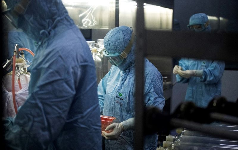 Researchers in protective suits work in a lab at the Yisheng Biopharma company, where researchers are trying to develop a vaccine for the COVID-19 coronavirus, in Shenyang, in China's northeast Liaoning province, on June 9, 2020. - China has mobilised its army and fast-tracked tests in the global race to find a coronavirus vaccine, and is involved in several of the dozen or so international clinical trials currently under way. (Photo by NOEL CELIS / AFP)