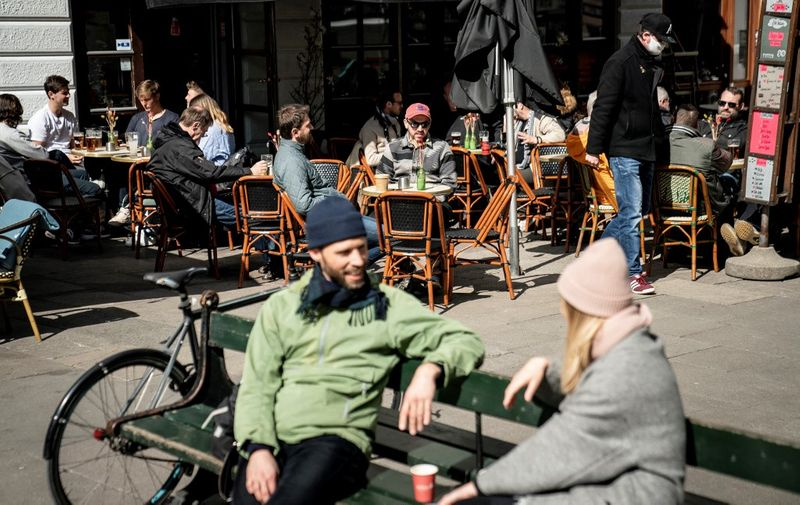 Guests enjoys outdoor service in Copenhagen on April 21, 2021, as restaurants, cafes and bars reopen amid the coronavirus (Covid-19) pandemic. - As of April 21, bars, cafes and restaurants reopen in Denmark. Serving stops at 10pm, the establishment must be closed from 11pm until 5am. (Photo by Mads Claus Rasmussen / Ritzau Scanpix / AFP) / Denmark OUT