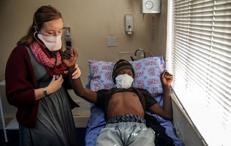 Doctor Pauline Howell (L) consults a patient known as Nxumalo, currently on the NIX treatment, at the Sizwe Tropical Diseases Hospital in Johannesburg, South Africa, on August 5, 2019. - A new treatment was approved on August 14, 2019 by the US Food and Drug Administration.  It cures highly drug-resistant strains of tuberculosis and drastically shorten the treatment period. The announcement was especially welcomed in South Africa, one of the countries with the highest number of TB cases. Of the more than 1.6 million TB deaths recorded every year, more than 75,000 are in South Africa alone. In 2017, South Africa recorded more than 322,000 active TB cases. (Photo by Michele Spatari / AFP)