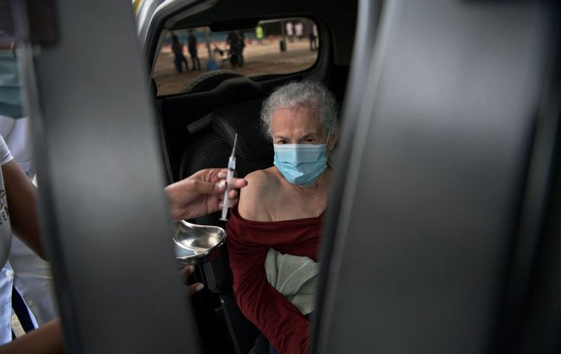 A Brazilian elderly woman receives a dose of the Coronavac vaccine at a drive through vaccination center at the Sambodrome Rio Carnival venue, in Rio de Janeiro, Brazil, on February 6, 2021. - Brazil's regulators gave conditional approval for Sinovac Biotech Ltd's shot, CoronaVac,  clearing the way for general use. Elderly and at risk members of the population have been given priority. (Photo by CARL DE SOUZA / AFP)
