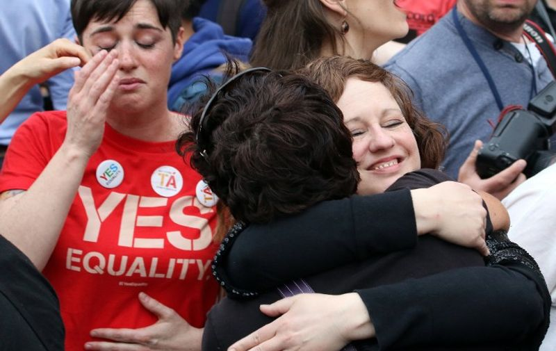 Supporters react outside Dublin Castle following the result of the same-sex marriage referendum in Dublin on May 23, 2015. Ireland on Saturday became the first country in the world to approve gay marriage by popular vote as crowds cheered in Dublin in a spectacular setback for the once all-powerful Catholic Church.    AFP PHOTO /  PAUL FAITH