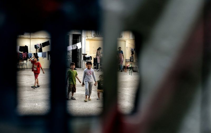 """Children are pictured through the gate of the courtyard of an abandoned school used by volunteers for hosting Syrian and Afghan refugees in Athens on July 1, 2016. Some 250 people live in self-management in the school of Athens city center, closed for three years. The families occupy three floors of the building, and twenty classrooms, where a tense sheets forest delineate areas of life and protect privacy. The squat was established in mid-March, when the sudden closure of their borders with the countries north of Greece makes it a trap for those who relied only cross to reach Germany or Sweden. Almost all e now living in dozens of camps set up in haste by the government. Some rent rooms. The others are squat. The government estimates about 1,500 the number of people living well into """"outdoor hospitality structures."""" / AFP PHOTO / ARIS MESSINIS"""
