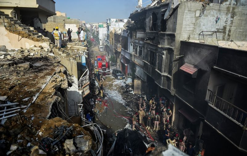 Rescue workers gather at the site after a Pakistan International Airlines aircraft crashed in a residential area in Karachi on May 22, 2020. - A Pakistani plane with nearly 100 people on board crashed into a residential area in the southern city of Karachi on May 22, killing several people on the ground. (Photo by Rizwan TABASSUM / AFP)