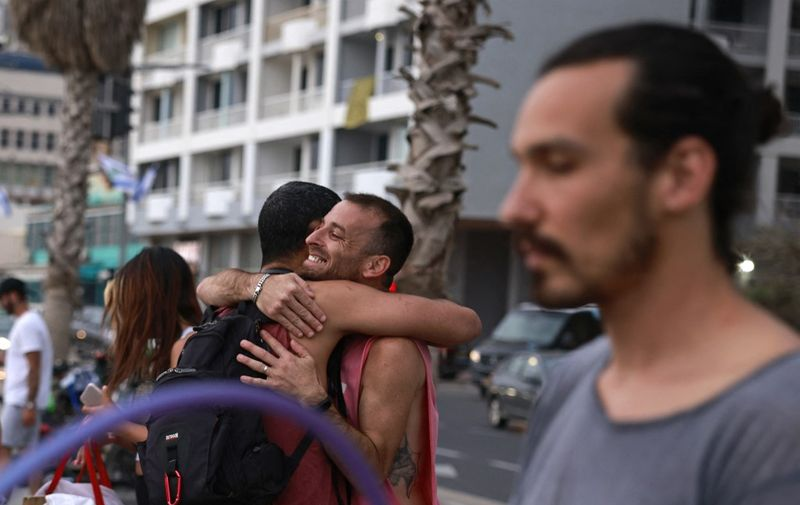 People embrace on the promenade in the Israeli coastal city of Tel Aviv on April 19, 2021, after authorities announced that face masks for COVID-19 prevention were no longer needed outside. - With more than half of the population fully vaccinated in one of the world's fastest COVID-19 inoculation campaigns, the number of coronavirus cases in Israel fell from some 10,000 new infections per day in mid-January to about 200 cases per day, which triggered an announcement from the Health Department on April 15 that face masks are no longer mandatory outdoors. (Photo by menahem kahana / AFP)