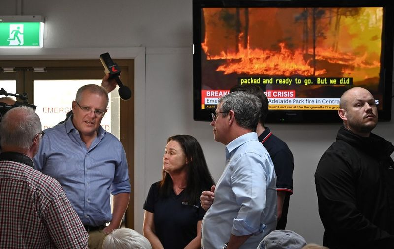 Australian Prime Minister Scott Morrison (L) speaks to residents and officials at an evacauation centre in Taree 350km north of Sydney on November 10, 2019 as firefighters try to contain dozens of out-of-control blazes that are raging in the state of New South Wales. - Three people are known to have have died and 150 homes have been destroyed as an unprecedented number of bushfires tore through eastern Australia. (Photo by PETER PARKS / AFP)