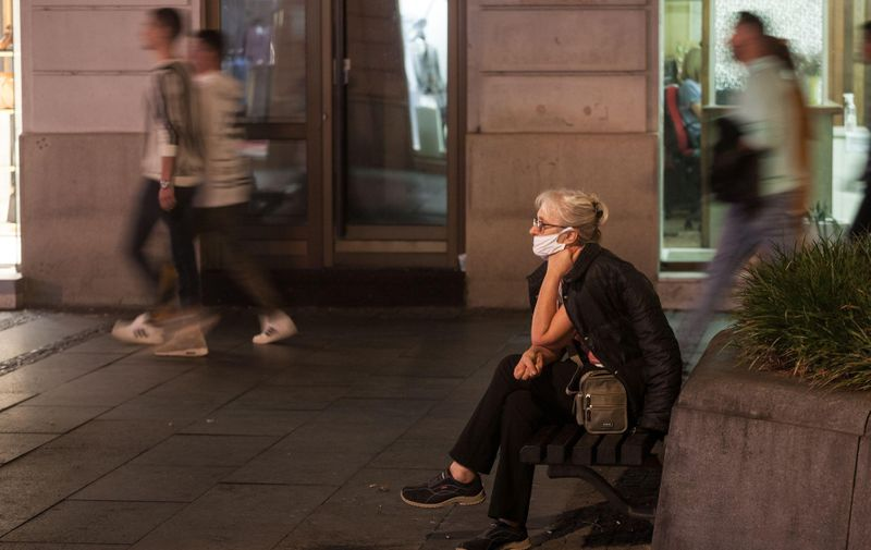 BELGRADE, SERBIA - OCTOBER 5, 2020: Old senior woman wearing a respiratory face mask sitting in a crowded street of Belgrade, during the coronavirus covid 19 health crisis.  Picture of a white caucasian senior woman in belgrade, serbia, sitting in the streets of Belgrade, capital city of Serbia, while wearing a respiratory face mask during the coronavirus health crisis.,Image: 566880342, License: Royalty-free, Restrictions: , Model Release: no