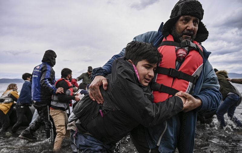 A man helps a young boy to walk after a dinghy with 54 Afghan refugees landed ashore the Greek island of Lesbos on February 28, 2020. - Turkey will no longer close its border gates to refugees who want to go to Europe, a senior official told AFP on February 28, shortly after the killing of 33 Turkish soldiers in an airstrike in northern Syria. (Photo by ARIS MESSINIS / AFP)