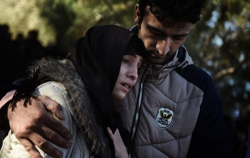 A couple react upon their arrival with other migrants and asylum seekers to the Greek island of Lesbos after crossing the Aegean Sea from Turkey on November 2, 2015. More than 218,000 migrants and refugees crossed the Mediterranean to Europe in October -- a monthly record and more than during the whole of 2014, the United Nations said. AFP PHOTO / ARIS MESSINIS