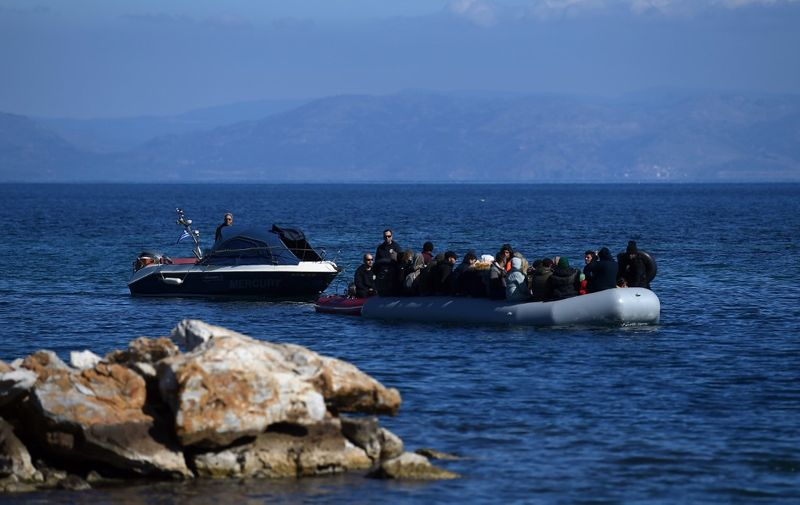 """Migrants are escorted upon their arrival on an inflatable boat at Lesbos island where  local residents will later prevent them from disembarking, on March 1, 2020. - Greece said Sunday it has blocked nearly 10,000 migrants at its border with Turkey, which opened its gates to Europe as tensions mount over its deepening conflict in Syria.  Migrant numbers have swelled along the rugged frontier after Turkey's president Recep Tayyip Erdogan said it """"opened the doors"""" to Europe in a bid to pressure EU governments over the conflict. (Photo by ARIS MESSINIS / AFP)"""