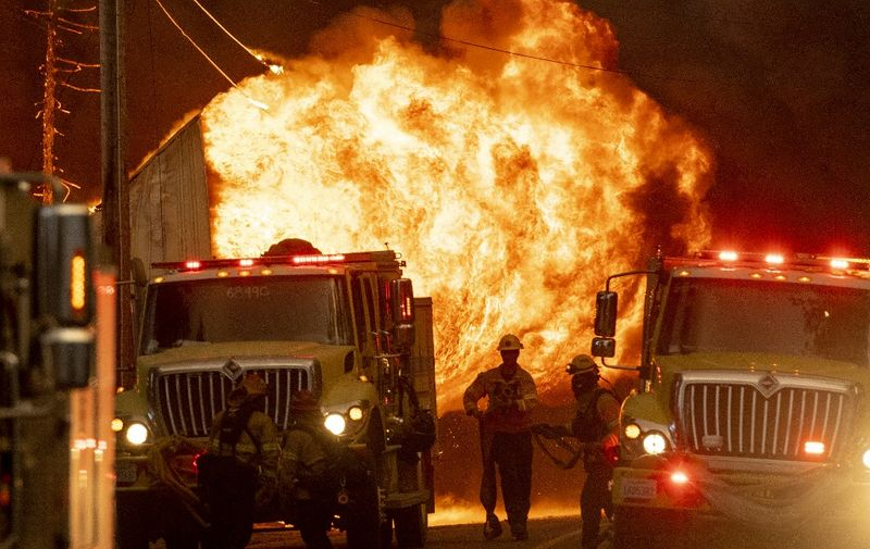 Firefighters work the scene as a home is engulfed in flames during the Dixie fire in Greenville, California on August 4, 2021. - The Dixie fire burned through dozens of homes and businesses in downtown Greenville and continues to forge towards other residential communities. Officials in northern California on August 4, 2021 warned residents of two communities in the path of the raging Dixie fire to evacuate immediately as high winds whipped the flames onwards. (Photo by JOSH EDELSON / AFP)