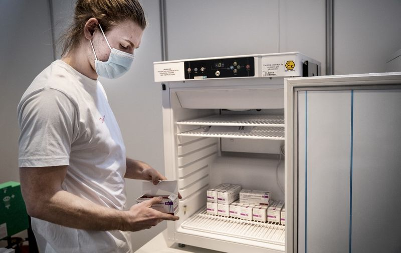 Medical personnel takes AstraZeneca vaccines out of the freezer at the Region Hovedstaden's vaccine center in Bella Center in Copenhagen on February 11, 2021, amid the ongoing coronavirus Covid-19 pandemic. (Photo by Liselotte Sabroe / Ritzau Scanpix / AFP) / Denmark OUT